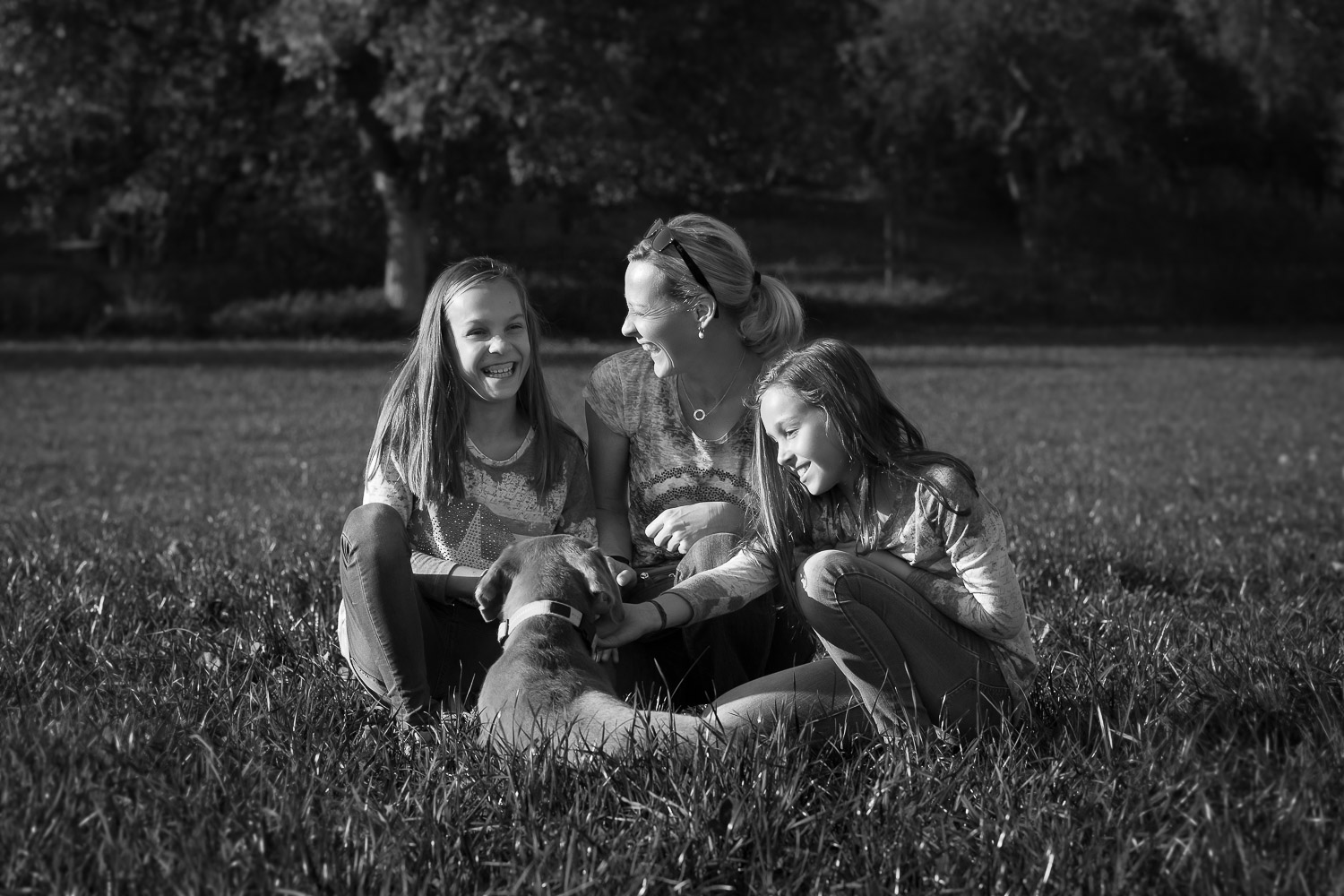 Mother an two Girls sitting with dog in the grass, black and white, portrait