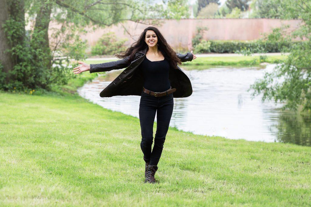 Ganzkörperportrait einer Frau im Park in einer Drehbewegung