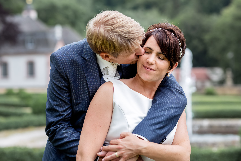 Groom kisses the bride in the garden of Schloss Weilerbach, Hochzeit, wedding, Andrea Schenke Photography