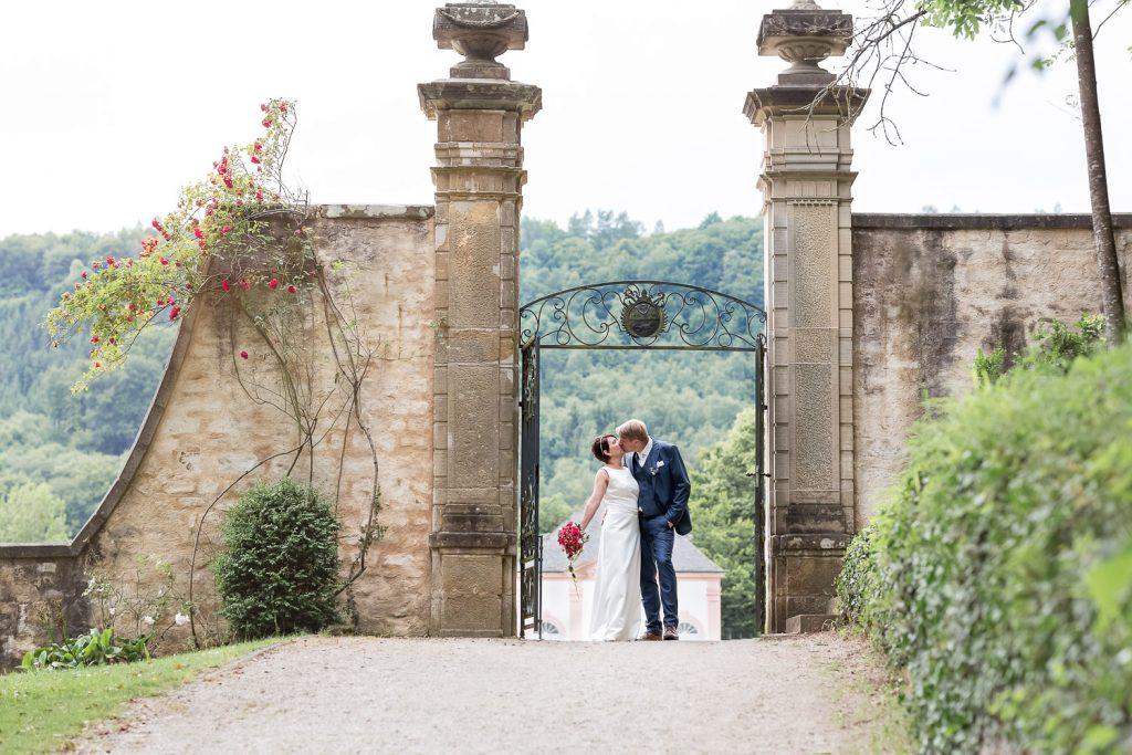 kissing couple next to the gate of Schloss Weilerbach, Hochzeit, Wedding, Andrea Schenke Photography, Hochzeitsfotograf Wittlich