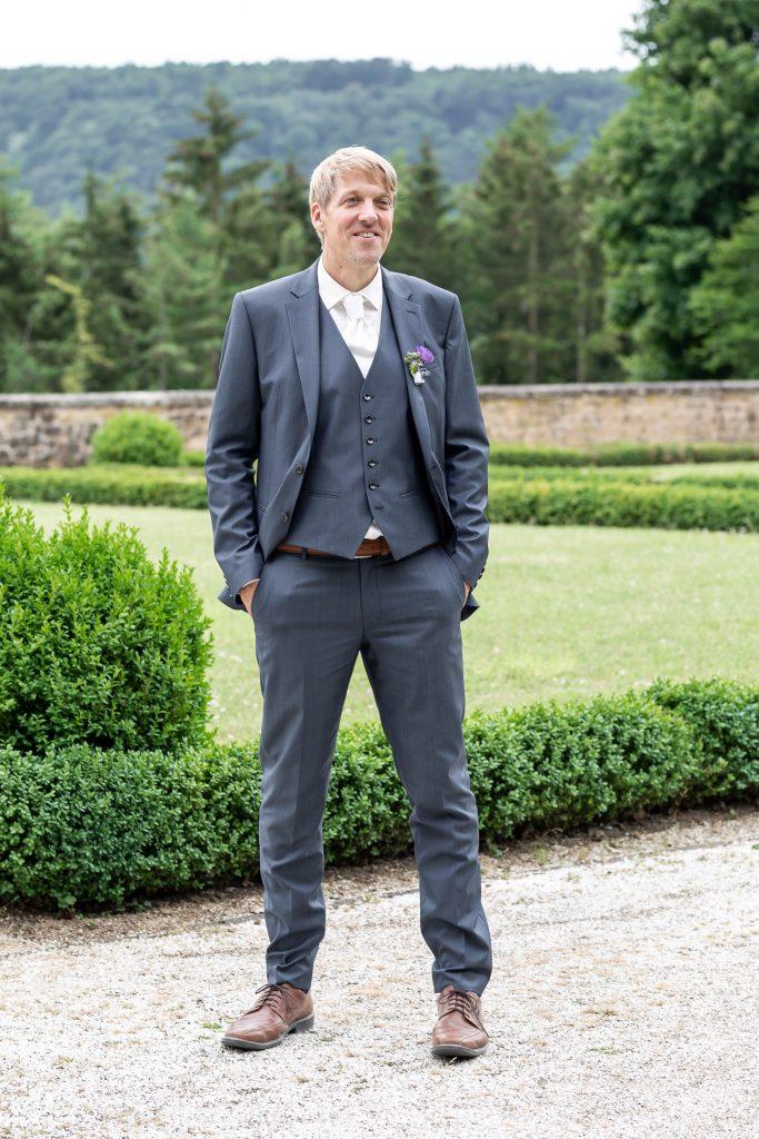groom standing in the garden of Schloss Weilerbach, Wedding, Hochzeit, Andrea Schenke Photography